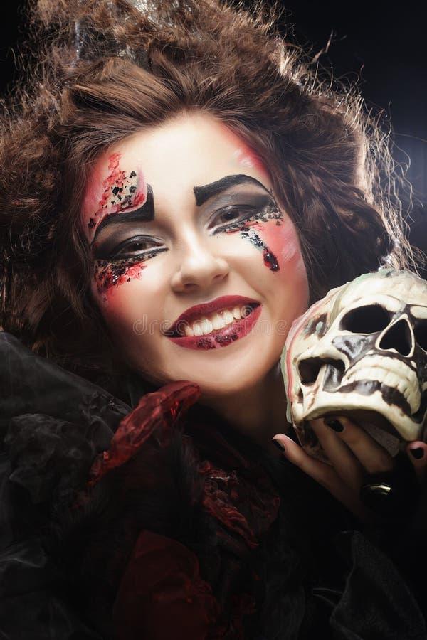 Jeune belle sorcière tenant un crâne photo stock