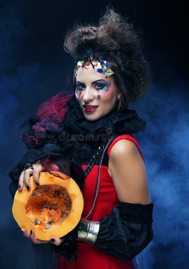 Jeune belle sorcière tenant un potiron au-dessus de fond foncé photo stock