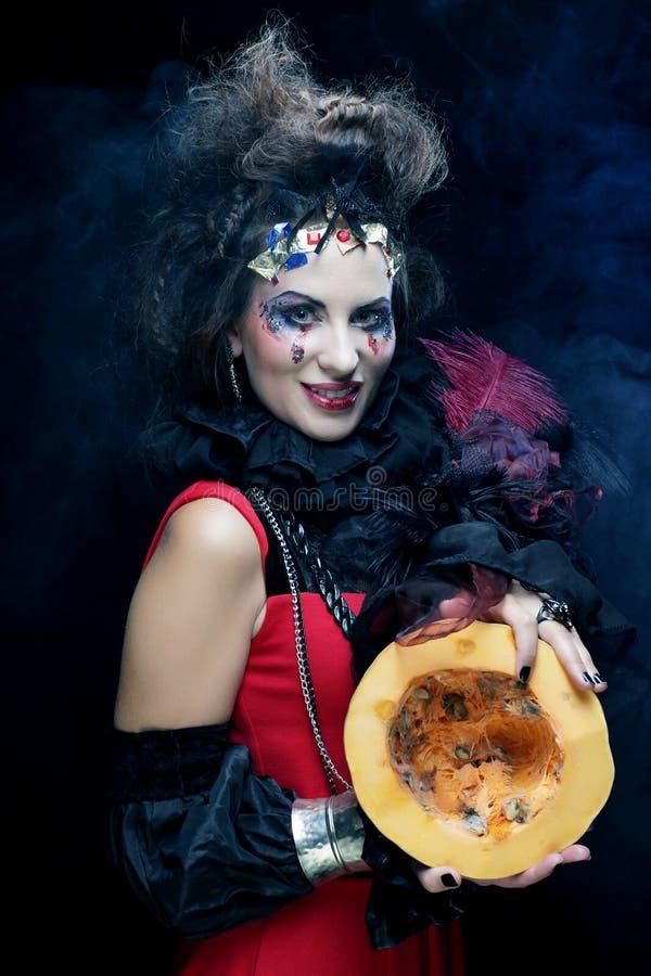 Jeune belle sorcière tenant un potiron au-dessus de fond foncé photos libres de droits