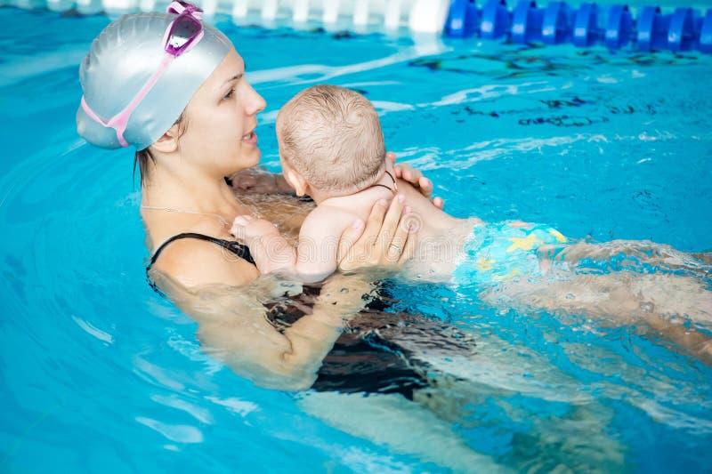 Jeune belle visite de mère une piscine avec son petit fils images libres de droits