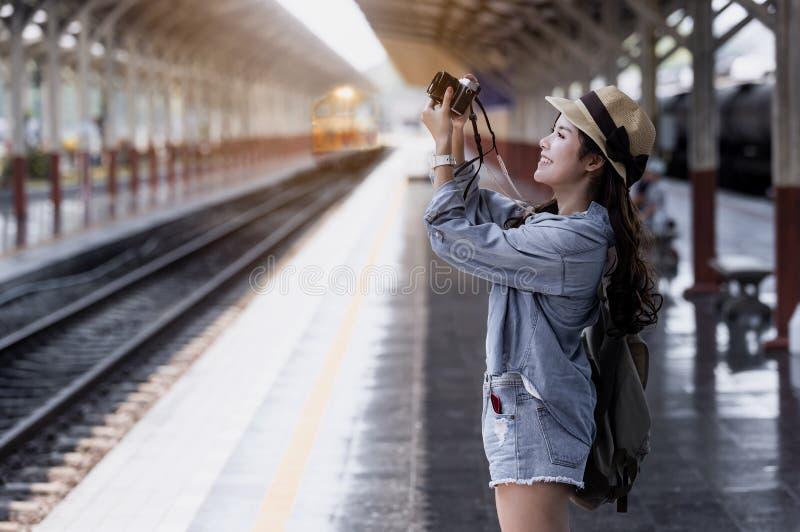 Jeune belle voyageuse de femme avec le sac à dos tenant l'appareil-photo photographie stock libre de droits