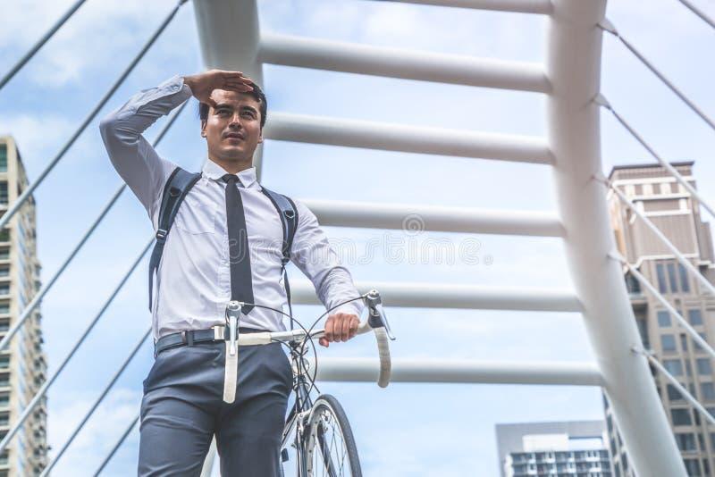 Jeune bicyclette d'équitation d'homme d'affaires à travailler dans la ville images stock
