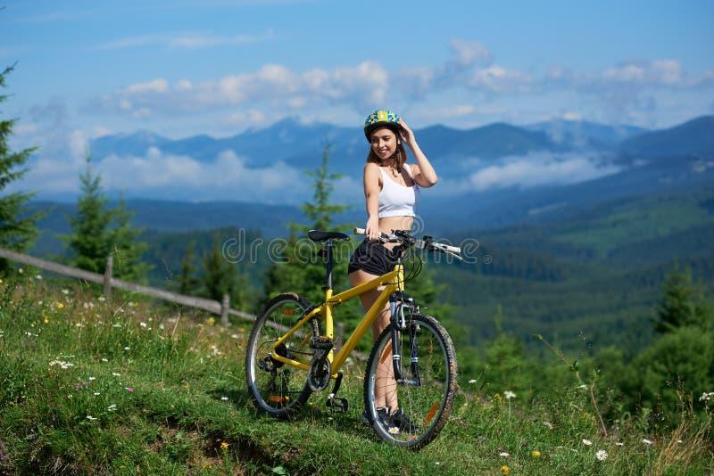 Jeune bicyclette heureuse d'équitation de femme dans les montagnes au jour d'été photographie stock libre de droits
