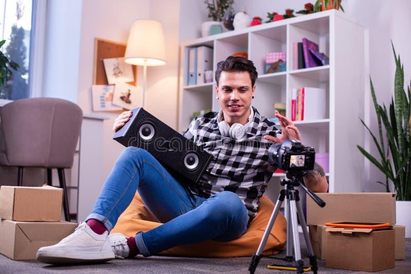 Jeune blogger actif appréciant le nouveau dispositif de musique et l'expliquant images libres de droits