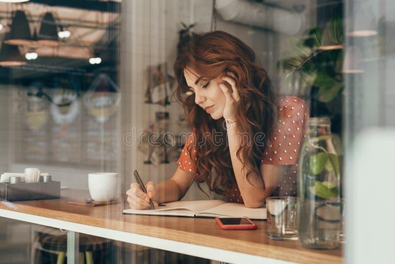 jeune blogger faisant des notes dans le carnet à la table avec la tasse de café photographie stock