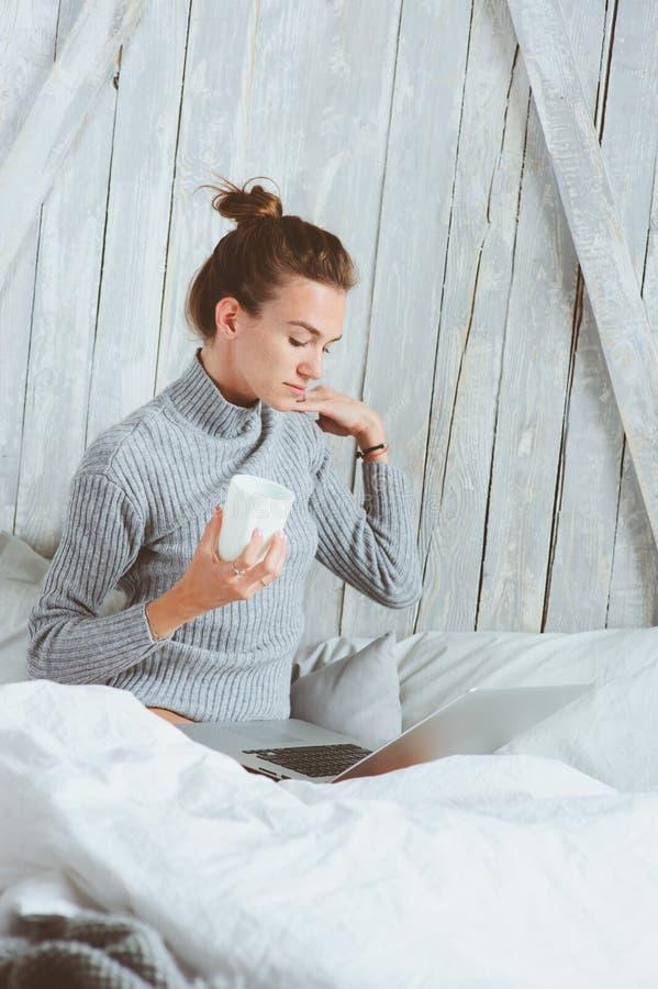 Jeune blogger ou femme d'affaires travaillant à la maison avec le media social, café potable dans le début de la matinée dans le  image stock