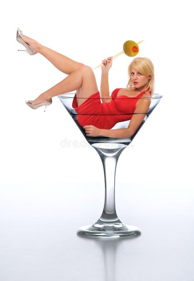 Jeune blond dans une glace de martini photo stock