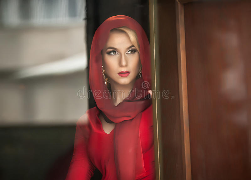 Jeune blonde avec du charme avec le chemisier rouge et foulard posant dans le cadre de porte Jeune femme magnifique sensuelle dan photos libres de droits