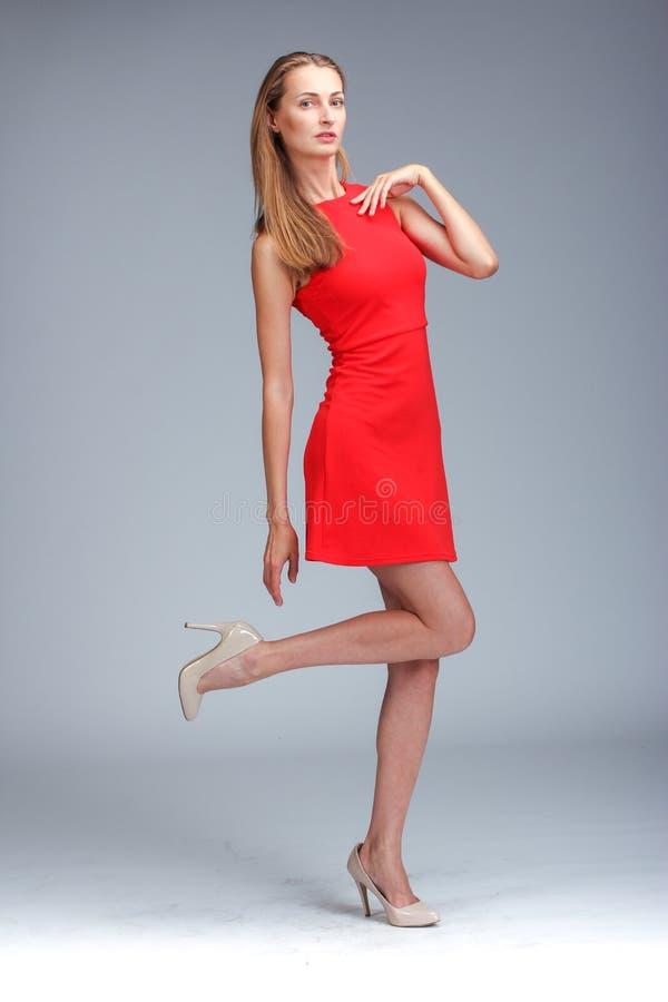 Jeune blonde caucasienne magnifique dans la pose rouge de robe images stock
