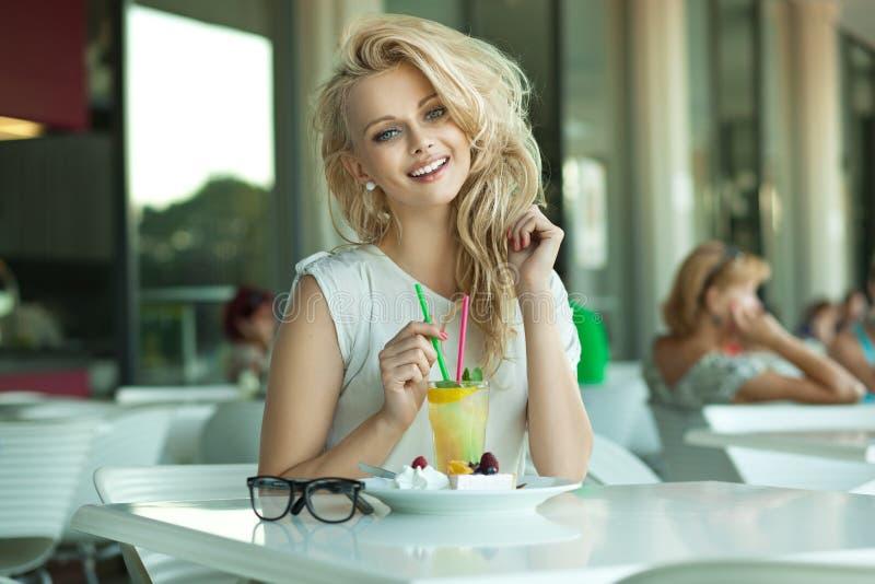 Jeune blonde gaie dans un bar de boissons images stock