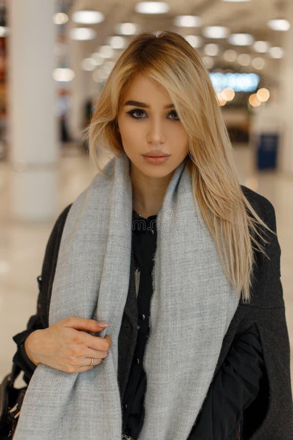 Jeune blonde sexy magnifique avec les yeux gris avec les lèvres sexy dans un manteau gris élégant avec une écharpe à la mode avec image stock