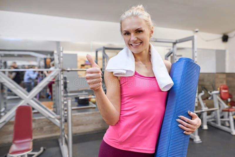 Jeune blonde sportive de femme dans le gymnase montrant des pouces vers le haut d'ok de signe Concept sain de mode de vie de spor photo libre de droits