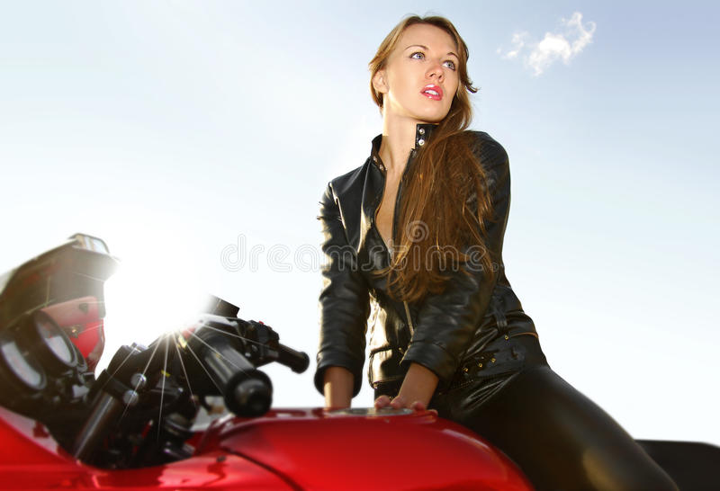 Jeune blonde sur une grande moto rouge image stock