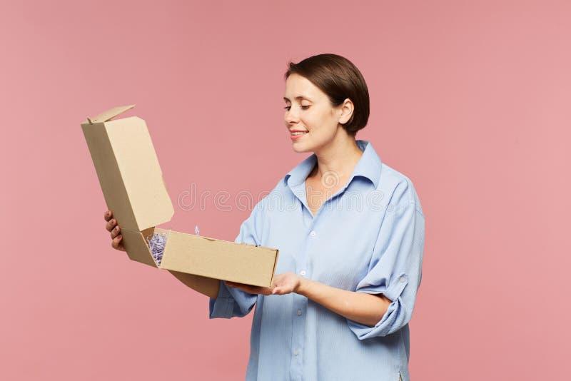 Jeune boîte étonnée heureuse d'ouverture de femme et regarder le cadeau photo stock