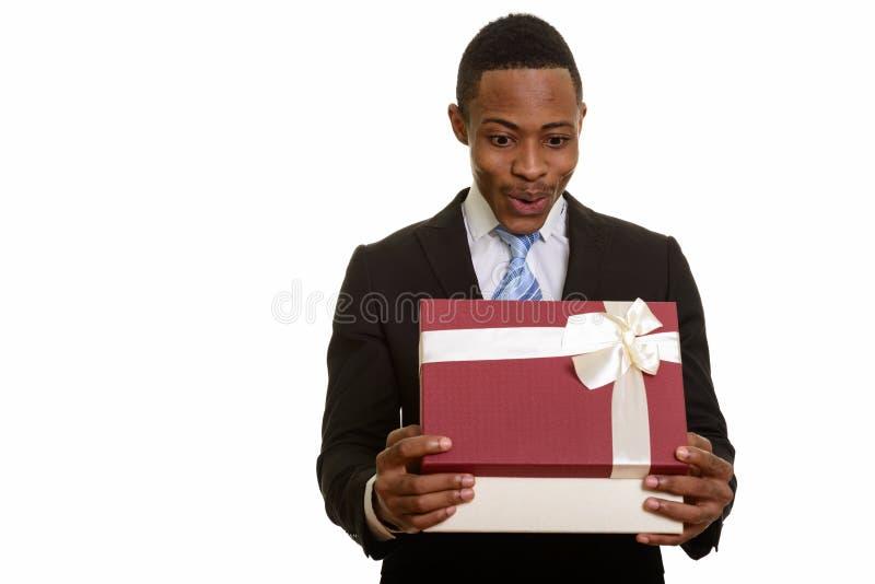 Jeune boîte-cadeau africain d'ouverture d'homme d'affaires et regard étonné image stock