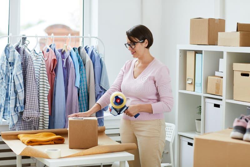 Jeune boîte de cachetage de directeur avec le ruban adhésif après casualwear de emballage photographie stock libre de droits
