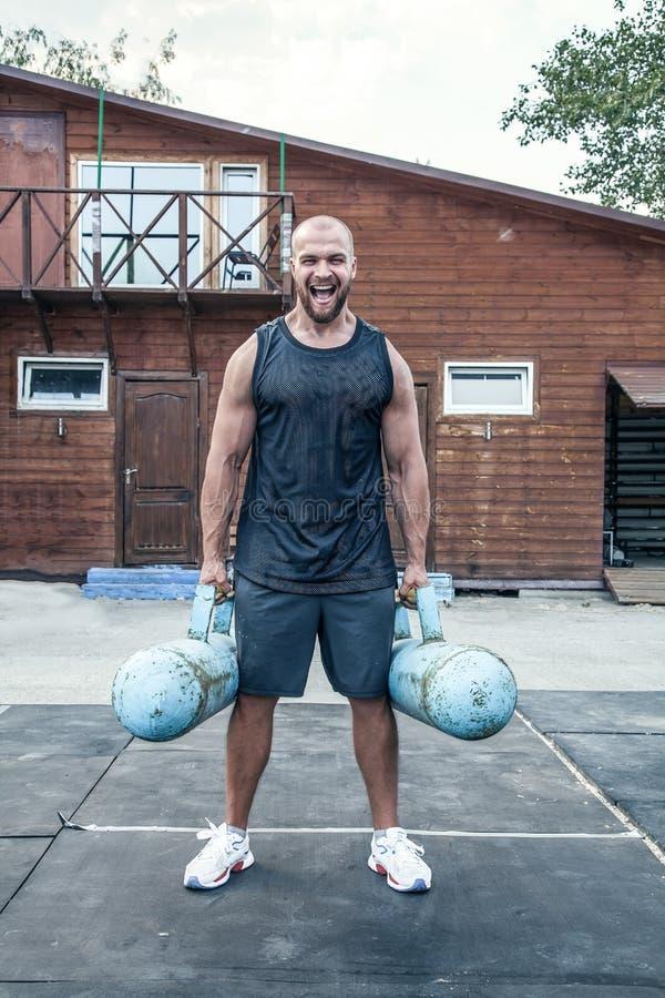 Jeune bodybuilder d'homme fort avec de grands barils dans des mains criant à la caméra photographie stock