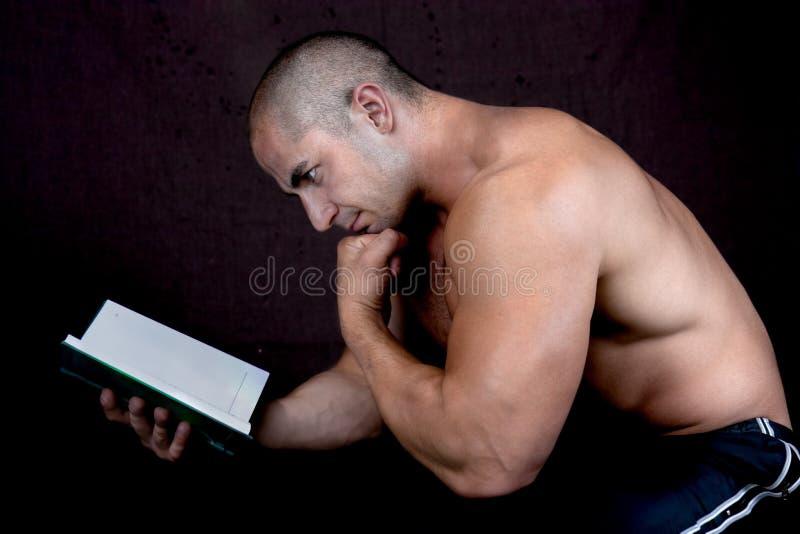 Jeune bodybuilder mâle attirant affichant le livre image libre de droits