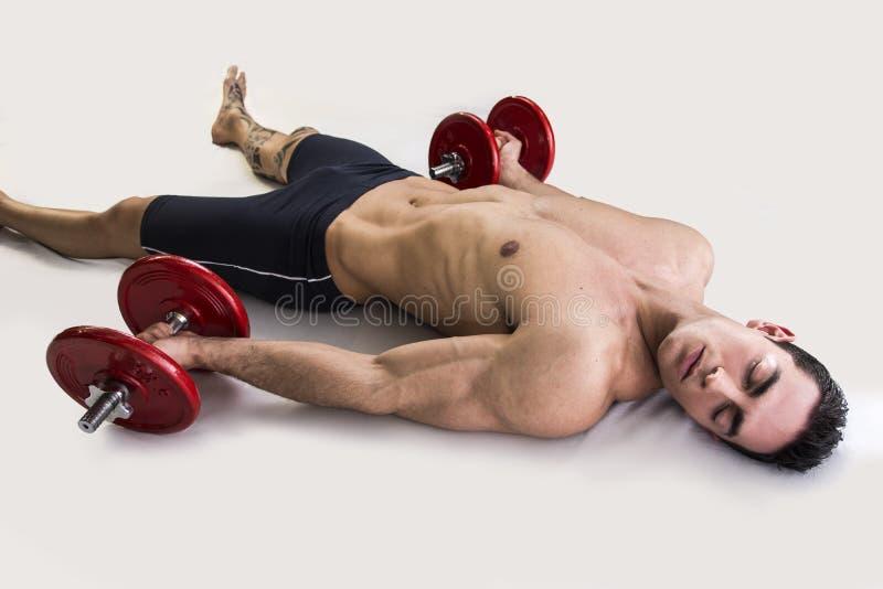 Jeune bodybuilder masculin épuisé se reposant sur le plancher photographie stock