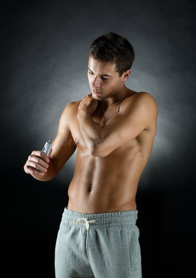 Jeune bodybuilder masculin appliquant le gel de soulagement de la douleur images libres de droits