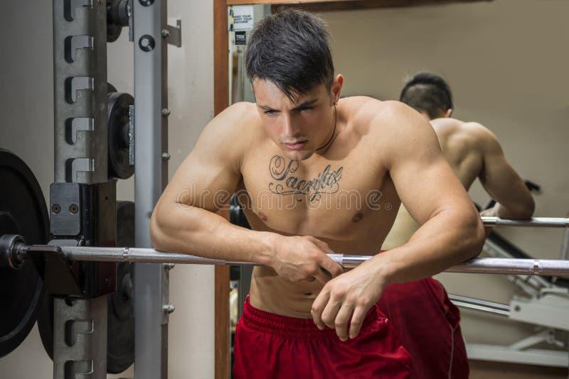 Jeune bodybuilder masculin fatigué se reposant entre les séances d'entraînement dans le gymnase photographie stock libre de droits