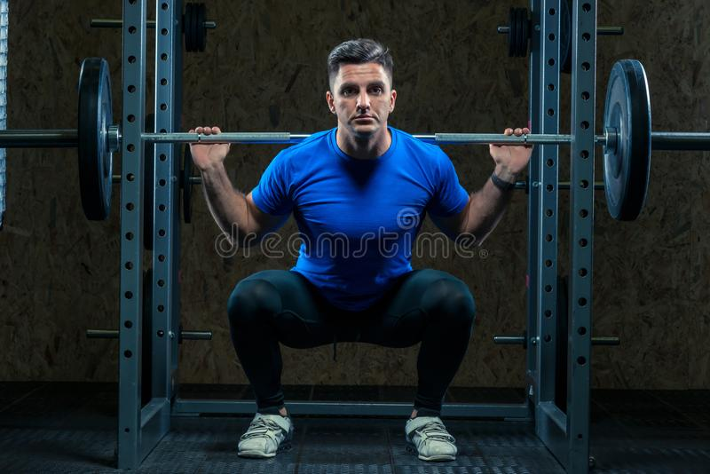 Jeune bodybuilder mignon avec un barbell dans le gymnase photos stock