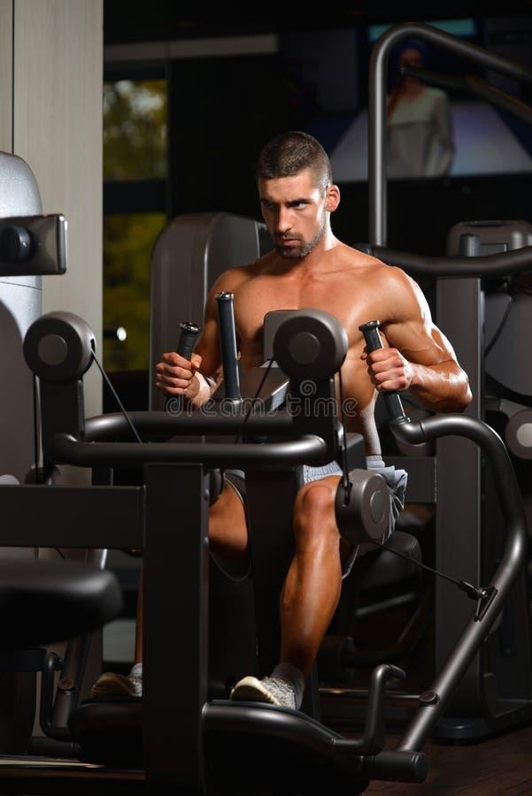 Jeune Bodybuilder s'exerçant de retour sur la machine photo libre de droits