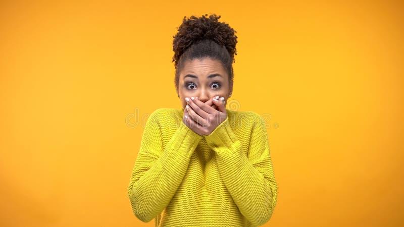 Jeune bouche afro-am?ricaine de fermeture de femme avec des mains, gardant le secret, bavardage images libres de droits