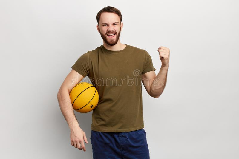 Jeune boule heureuse et enthousiaste de panier de participation d'homme au-dessus de fond d'isolement photo stock