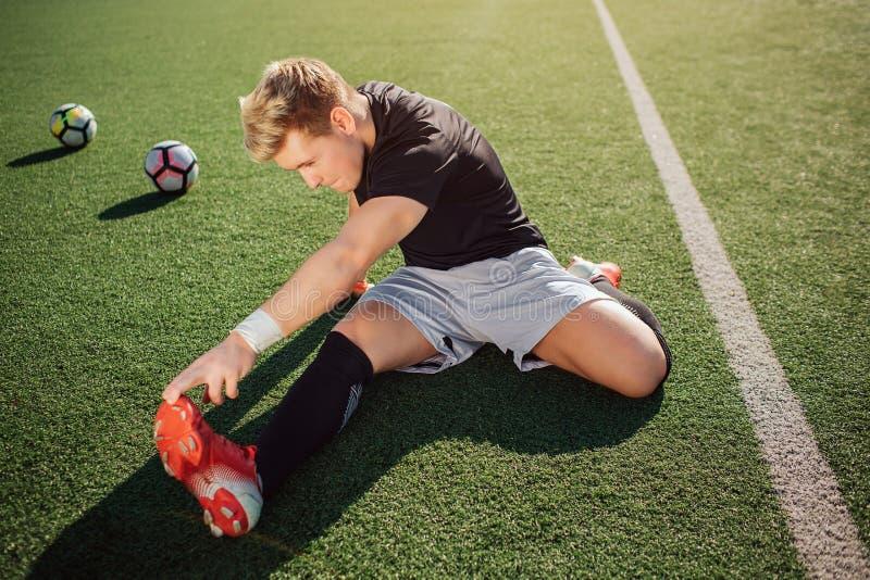 Jeune bout droit blond de joueur de football dehors sur la pelouse Il atteint des pieds avec la main Le type est concentré sur l' image libre de droits