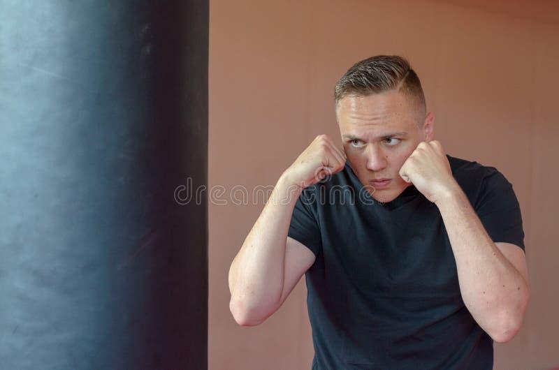 Jeune boxeur établissant avec un sac de poinçon photo stock