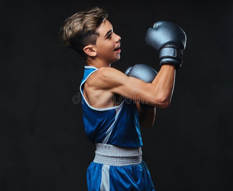 Jeune boxeur beau pendant les exercices de boxe, concentrés sur le processus avec le massage facial concentré sérieux D'isolement image stock