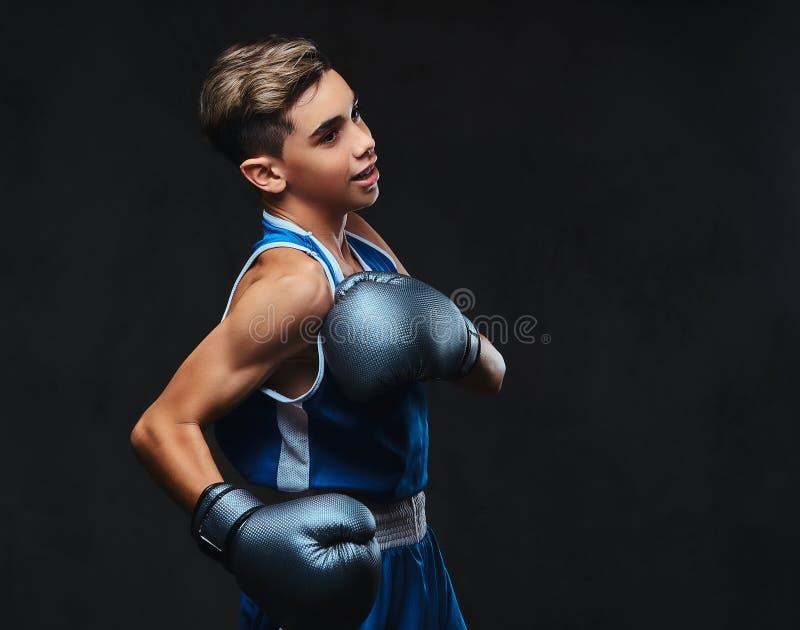 Jeune boxeur beau pendant les exercices de boxe, concentrés sur le processus avec le massage facial concentré sérieux D'isolement photos stock
