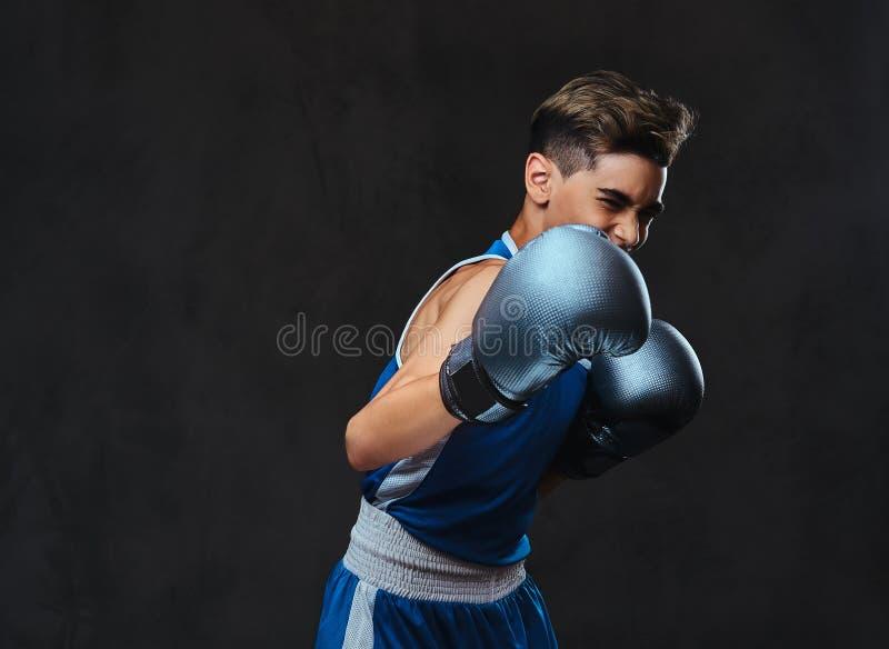 Jeune boxeur beau pendant les exercices de boxe, concentrés sur le processus avec le massage facial concentré sérieux D'isolement photos libres de droits