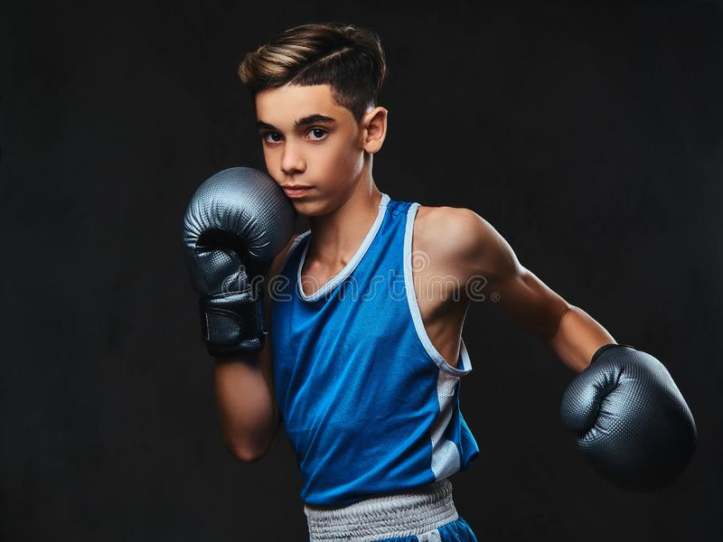 Jeune boxeur beau pendant les exercices de boxe, concentrés sur le processus D'isolement sur le fond foncé image libre de droits