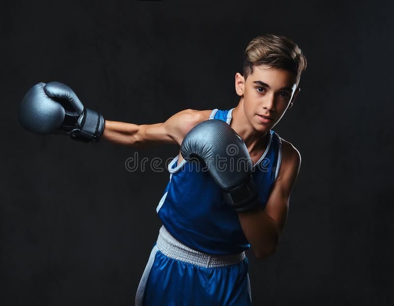 Jeune boxeur beau pendant les exercices de boxe, concentrés sur le processus D'isolement sur le fond foncé images libres de droits