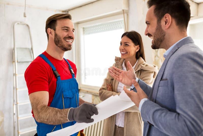 Jeune bricoleur de sourire de couples et de constructeur parlant des détails photo stock