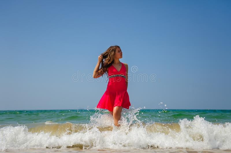 Jeune brune aux cheveux longs sexy dans la position rouge de robe dans les vagues avec la mousse blanche sur le fond de mer et le image stock