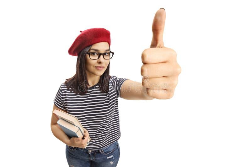 Jeune brune avec un béret tenant des livres et montrant le pouce  images stock
