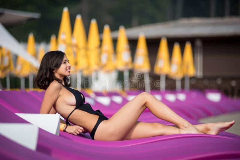 Jeune brune avec un corps parfait dans un bikini noir se trouvant sur un canapé pourpre sur le lieu de villégiature luxueux photos stock