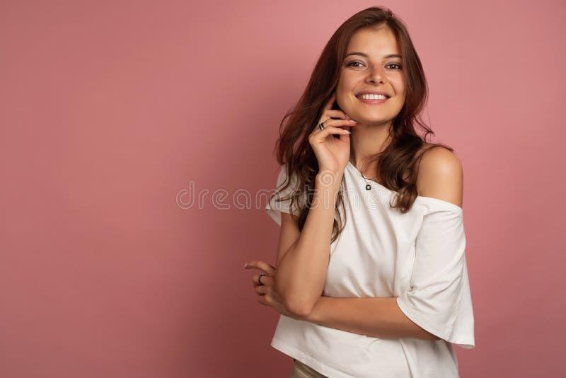 Jeune brune dans les sourires blancs d'un T-shirt regardant largement directement la caméra, fond rose photo libre de droits