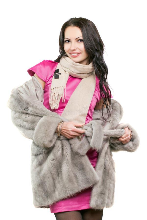 Jeune brune de sourire dans un manteau de fourrure photos stock