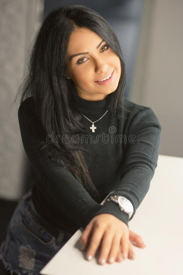 Jeune brune de sourire posant dans un studio photographie stock