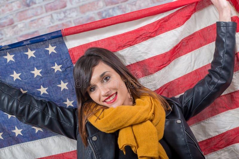 Jeune brune devant le drapeau américain photo stock