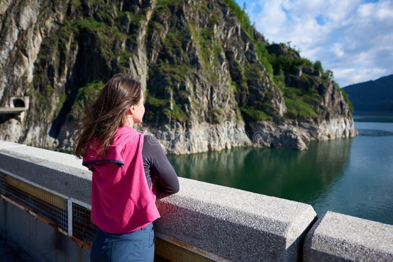 Jeune brune examinant loin la distance admirant la beauté des roches et du lac herbeux verts Vidraru en Roumanie photos stock