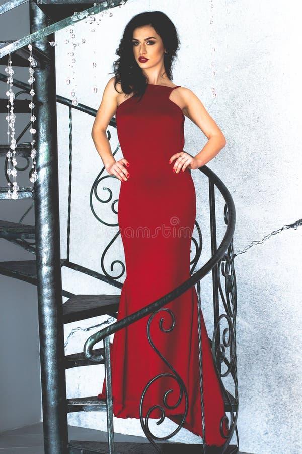 Jeune brune modèle dans la pose rouge de robe photo stock