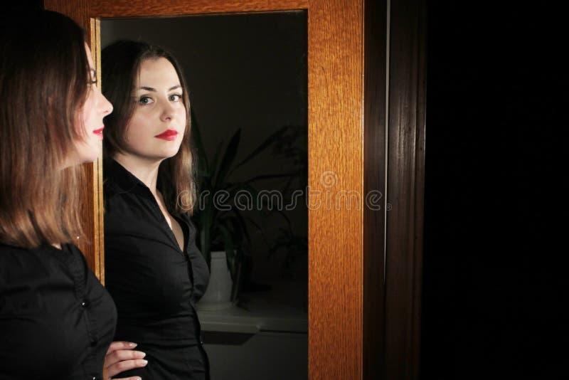 Jeune brune posant devant le miroir photo libre de droits