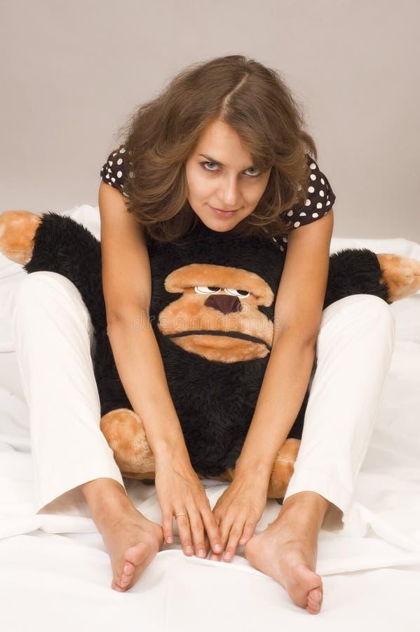 Jeune brunette infantile avec le singe image stock