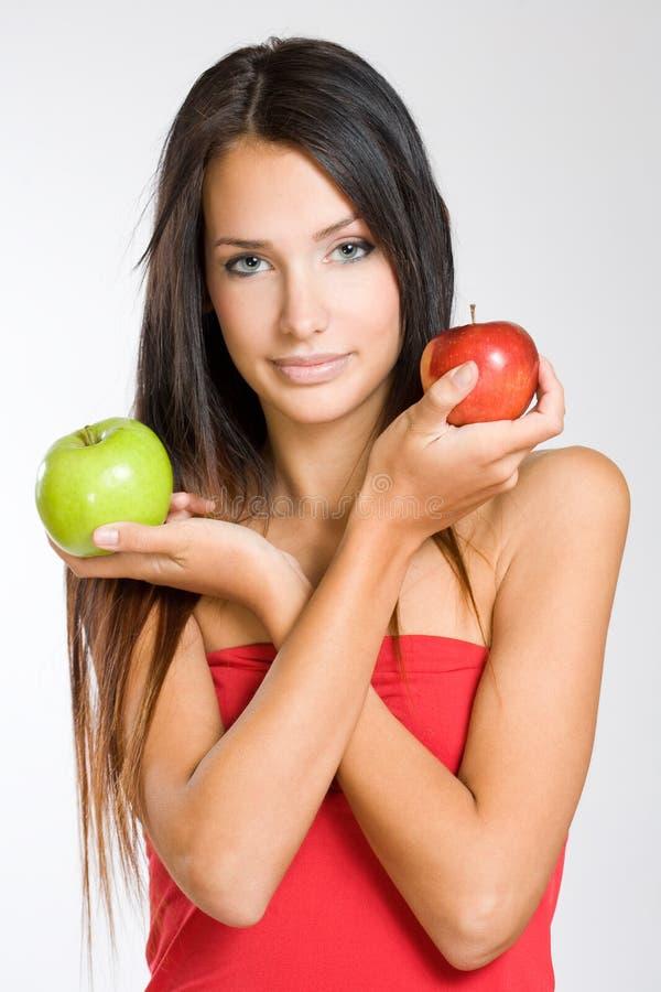 Jeune brunette mignon retenant deux pommes. photo libre de droits