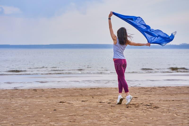 Jeune brunette minuscule en sport faisant du sport en dansant avec une écharpe bleue Une femme est fiancée sur le rivage sablonne photo stock